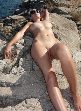 Lilou pose nue sur les rochers de la palge pour le plaisir de son mari